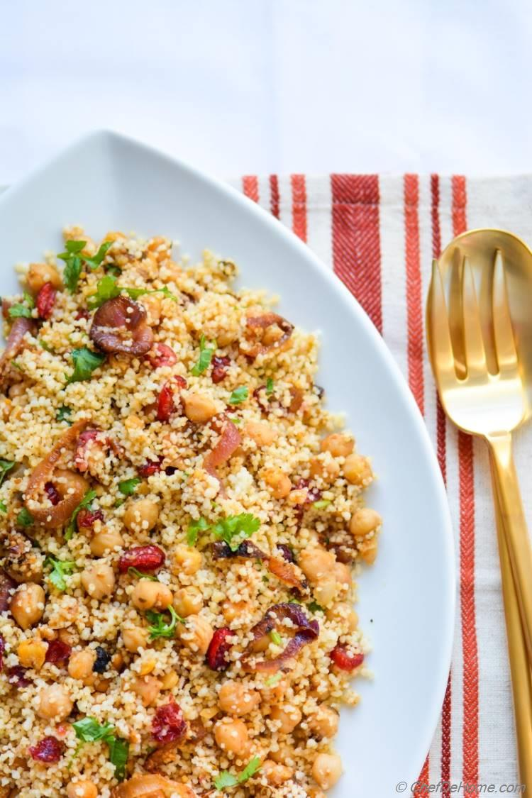 Warm and comforting bowl of Couscous with spiced chickpeas, and caramelized onions, with some festive sweetness and color from cranberries.