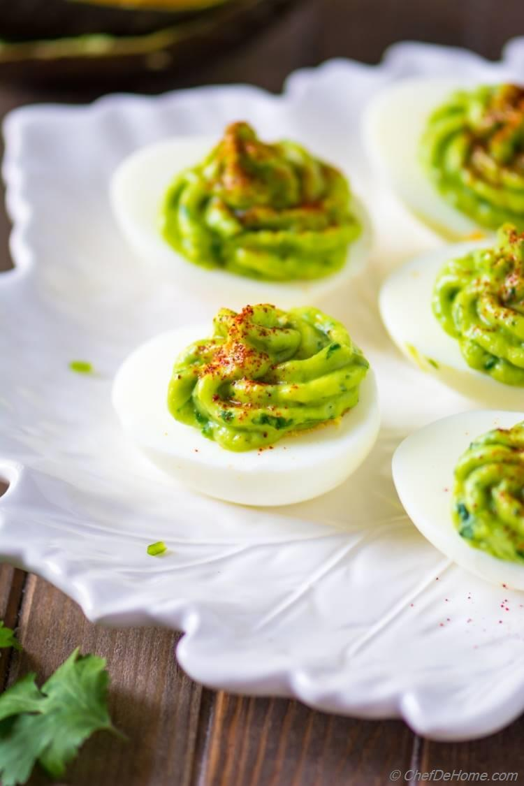 Spicy and healthy deviled eggs topped with avocado sauce