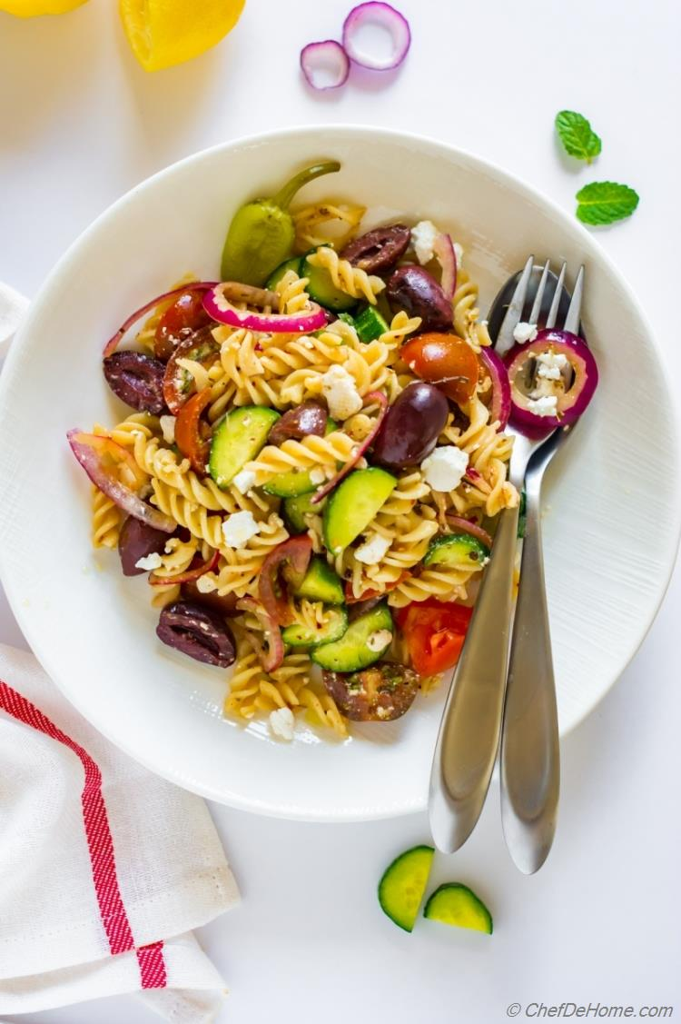 Greek salad with fussili pasta red onion olives and cucumber